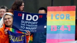 Lin Davis, of Juneau, Alaska, shown wearing an orange rain coat, holds signs supporting gay marriage during a news conference Friday, Oct. 10, 2014, outside the federal courthouse in Anchorage, Alaska.  AP