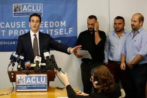 Attorney Stephen Rosenthal, left, explains to the media the real-life consequences of the federal court ruling as Tony Lima, executive director of SAVE, and same-sex couple, Carlos Andrade and husband, Christian Ulvert, right, stands near by. ACLU held a press conference in reaction a federal district court ruling the state's same-sex marriage ban is unconstitutional on Thursday, Aug. 21, 2014. CARL JUSTE MIAMI HERALD STAFF